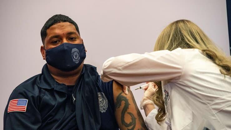 یک افسر پلیس لمریکایی در حال تزریق واکسن.