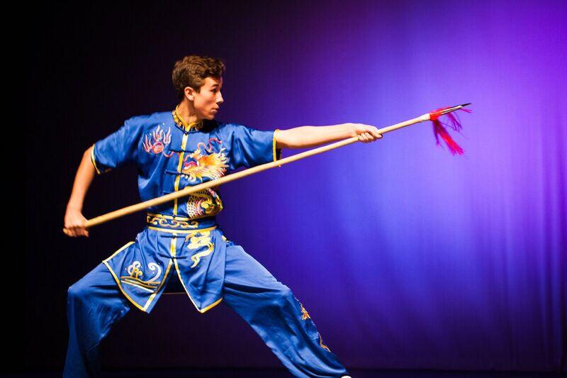 هنرجوی ووشو سبک چانگ چوان با لباس و نیزه نمایشی در حال اجرای فرم نیزه.