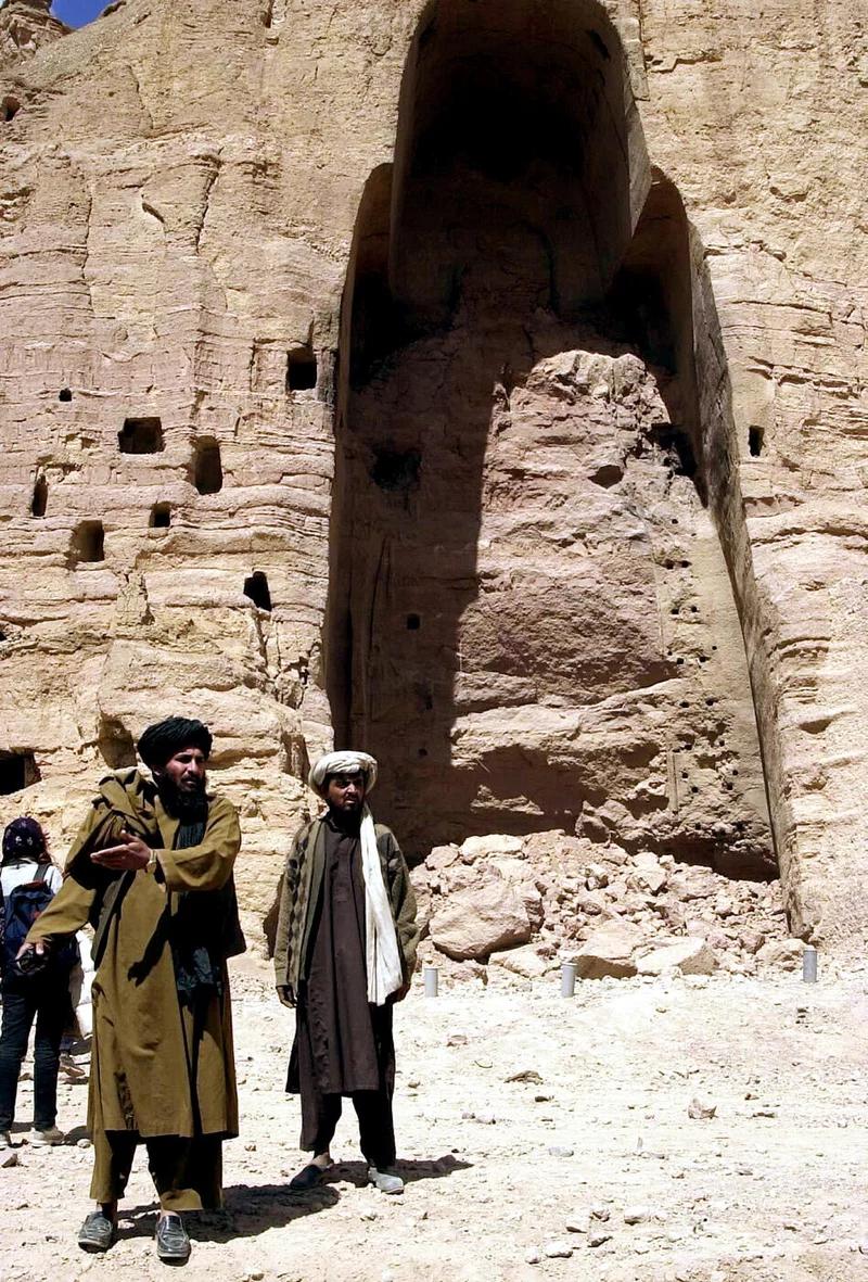 طالبان افغان در مقابل طاقچه خالی که یکی از دو مجسمه بزرگ بودا را نگه داشته بود ، طالبان در مارس 2001 در بامیان منفجر کردند.