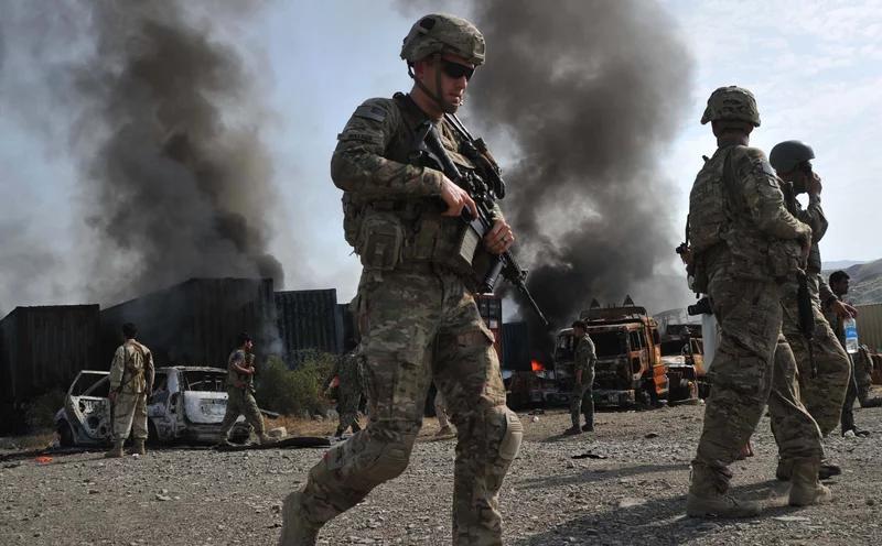 یک سرباز آمریکایی از کنار کامیون های سوزانده شده در محل حمله انتحاری در ولایت ننگرهار افغانستان در سال 2014 می گذرد.