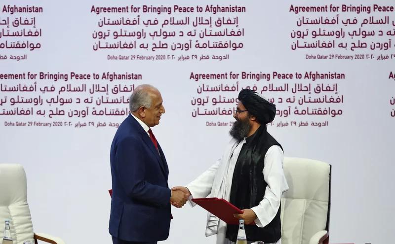 زلمی خلیلزاد ، نماینده ویژه ایالات متحده برای آشتی در افغانستان و ملا عبدالغنی برادر بنیانگذار طالبان پس از امضای توافقنامه صلح آمریکا و طالبان در دوحه ، قطر ، در 29 فوریه 2020 دست می دهند.