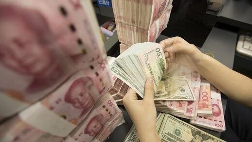 یک کارمند بانک در حال شمردن دلار آمریکا و یوان چین