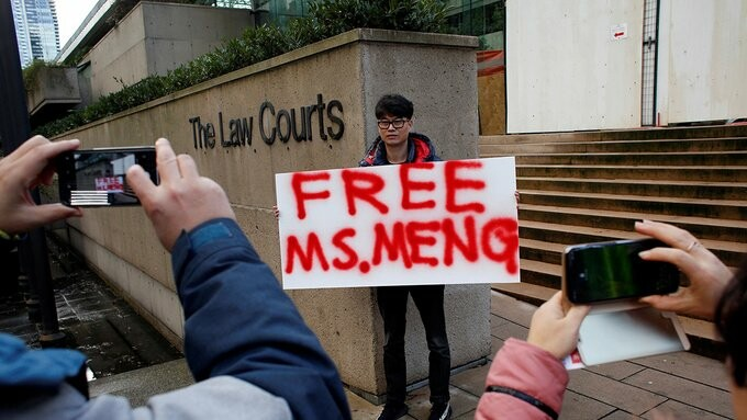 مردی در هنگام برگزاری جلسه دادرسی درخواست وثیقهی منگ وانژو، تابلوی درخواست آزادی وی را در خارج از دادگاه کانادا نگهداشته است.