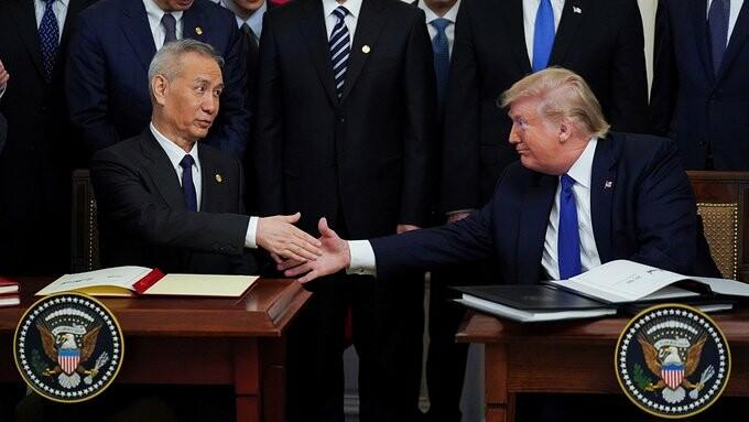 معاون نخستوزیر لیو و رئیس جمهور ترامپ پس از امضای توافق «فاز یک» با یکدیگر دست میدهند.
