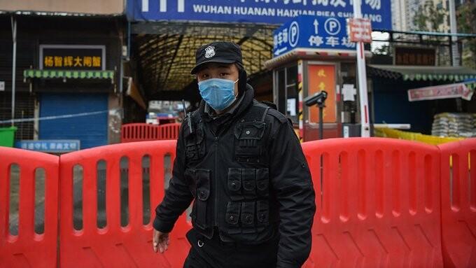 یک افسر پلیس از بازار حیوانات در ووهان چین محافظت میکند، جایی که ویروس کرونا در ژانویه گزارش شد.