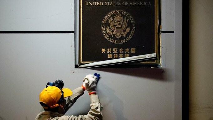یک کارگر پلاک کنسولگری ایالات متحده در چنگدو را از دیوار برمیدارد.